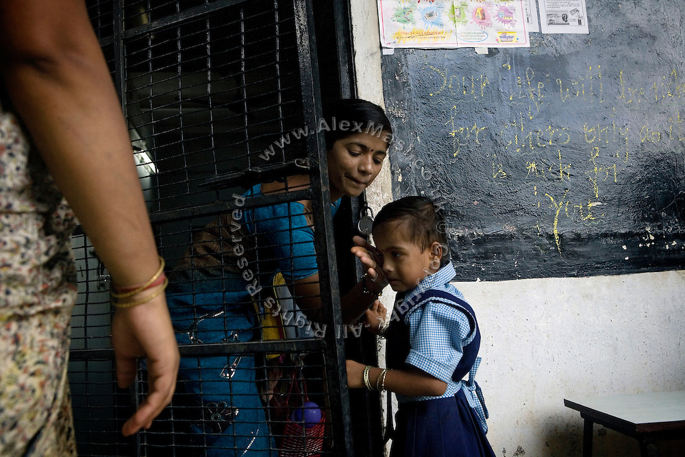 .A teacher is taking care of a child just arrived in the morning to the school run by the fast-growing Spanish NGO in Mumbai, India..