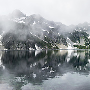 Chair Peak (elevation 6238 feet) and fog reflect in Snow Lake (4400 feet) in Alpine Lakes Wilderness Area, Mt. Baker-Snoqualmie National Forest Trail #1013, in the Cascade Range of Washington, USA. Take Interstate 90 Exit #52 westbound or Exit #53 eastbound and follow signs to Alpental Road ski area parking lot and Snow Lake trailhead. To avoid crowds at this popular trail, start early and avoid sunny weekends. The trail down from the saddle viewpoint to Snow Lake is often snow covered through July 4. This image was stitched from 3 overlapping photos.