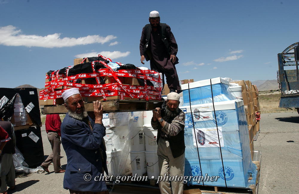 """Afghan men carry a pallet of humanitarian aide supplies after it was unloaded from an Antonov-12, a Russian cargo aircraft, at the Kabul airport on Thursday afternoon, May 23, 2002. The Geshundheit Instititute, founded by Dr. Hunter """"Patch"""" Adams, Lufthansa Cargo, and DHL Worldwide Express collaborated to ship medicines, food and orthopedic supplies to the Indira Ghandi Children's Hospital, clinics and orphanages in Kabul. The German NGO (Non Governmental Organization) Hammer Forum supervised the distribution of the donated supplies from various non-profit organizations in the U.S. and The Netherlands."""