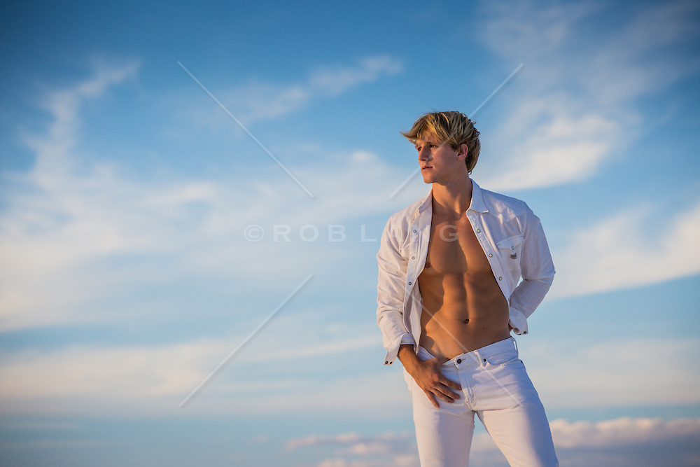 hot blond guy with an open shirt at sunset