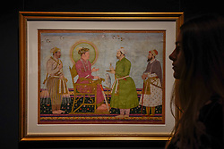 © Licensed to London News Pictures. 21/04/2017. London, UK.  A staff member views a calligraphic panel showing Jahangir offering jewels to Asaf Khan, India, late 17th century, (est. GBP 60-80k), at a preview at Sotheby's, New Bond Street, of upcoming sales of Arts of the Islamic World, 20th century Middle East Art and Orientalist art. Photo credit : Stephen Chung/LNP