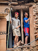 06 AUGUST 2015 - KATHMANDU, NEPAL: Men rebuild a house near Seto Machindranath Temple in Kathmandu. The home was one of thousands in the area damaged in the Nepal Earthquake. The Nepal Earthquake on April 25, 2015, (also known as the Gorkha earthquake) killed more than 9,000 people and injured more than 23,000. It had a magnitude of 7.8. The epicenter was east of the district of Lamjung, and its hypocenter was at a depth of approximately 15km (9.3mi). It was the worst natural disaster to strike Nepal since the 1934 Nepal–Bihar earthquake. The earthquake triggered an avalanche on Mount Everest, killing at least 19. The earthquake also set off an avalanche in the Langtang valley, where 250 people were reported missing. Hundreds of thousands of people were made homeless with entire villages flattened across many districts of the country. Centuries-old buildings were destroyed at UNESCO World Heritage sites in the Kathmandu Valley, including some at the Kathmandu Durbar Square, the Patan Durbar Squar, the Bhaktapur Durbar Square, the Changu Narayan Temple and the Swayambhunath Stupa. Geophysicists and other experts had warned for decades that Nepal was vulnerable to a deadly earthquake, particularly because of its geology, urbanization, and architecture.     PHOTO BY JACK KURTZ