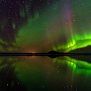 "The northern lights, or aurora borealis, shine over and are reflect in Lake Mývatn  in northern Iceland. The lake, formed during a lava eruption 2,300 years ago, contains numerous lava pillars and rootless vents, called pseudocraters. Mývatn is Icelandic for ""midge lake,"" and denotes the tremendous number of midge flies found in the area. The aurora borealis, frequently visible during the winter months in Iceland, is caused by charged particles from the sun crashing into the Earth's atmosphere."