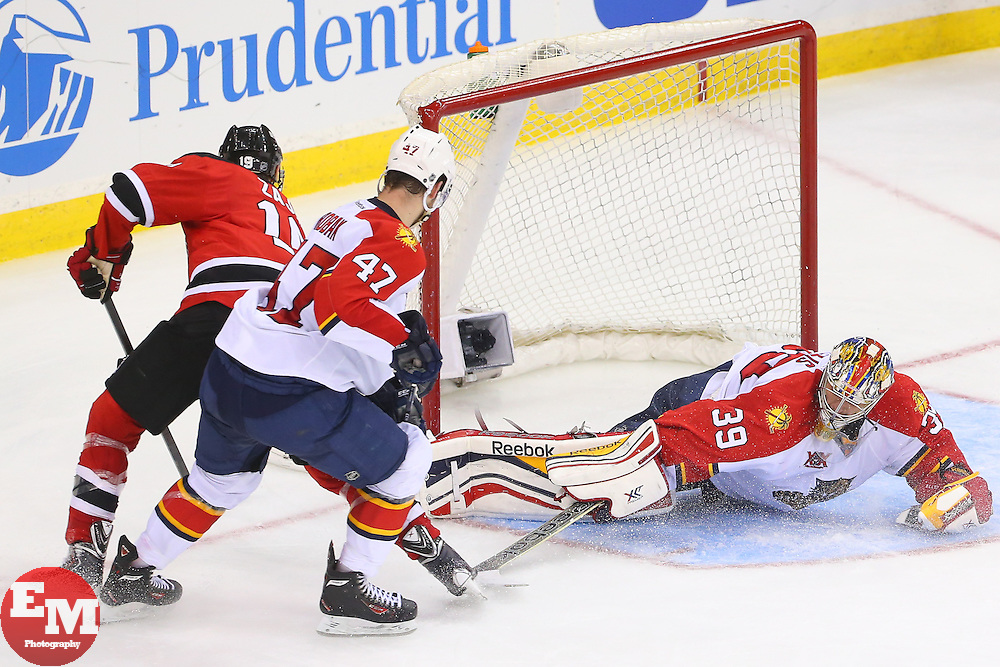 Mar 31, 2014; Newark, NJ, USA; New Jersey Devils center Travis Zajac (19) gathers the puck after a save by Florida Panthers goalie Dan Ellis (39) during the third period at Prudential Center. The Devils defeated the Panthers 6-3.