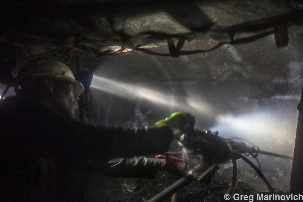 Rowland Shaft, Lonmin Marikana Aug 2, 1013. Humidy and a fine dusty mist envelope a working stope as a driller works, pouring sweat, Level 31. Photo Greg Marinovich