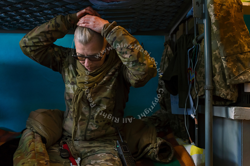 Julia Paevska is tying her hair, sitting on a bunk bed while visiting soldiers at a military base near the frontline in Myronivs'kyi.