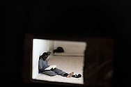 Libia, Tripoli: An African migrant reads the Koran inside his cell through the hole of an iron door at Abu Salim detention center for illegal migrants. Alessio Romenzi