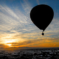 A hot air balloon piloted by Gary Cass drifts southward across the city of Yuma during a early morning flight Wednesday to help promote the 17th annual Colorado River Crossing Balloon Festival.