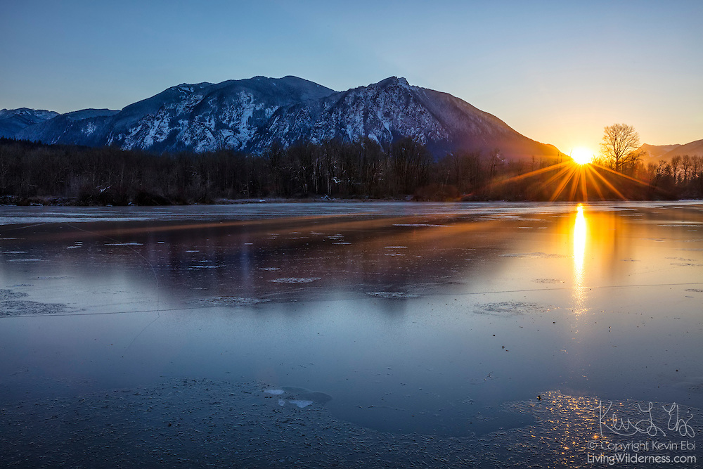 The sun's rays stretch across the frozen Borst Lake as the sun rises alongside Mount Si, a 4167-foot (1270-meter) mountain in North Bend, Washington.
