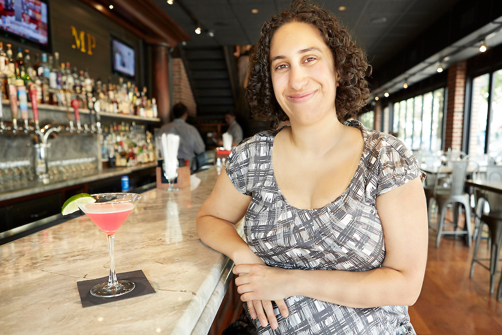 Portrait photograph of Indian woman with pink cocktail sitting inside bar