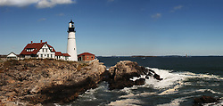 Daytime shot of Portland Head lighthouse panorama with bluffs and Atlantic Ocean