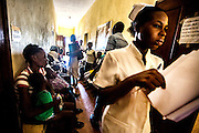 A nursing student walks through the crowded halls of the Healing Art Missions clinic in Dumay Haiti. Patients often begin arriving at the clinic from all parts of Dumay at 6 in the morning to see a doctor. They will wait for hours outside to be checked in, have their vitals taken and finally to see a doctor.