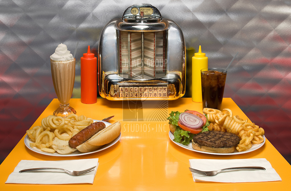 1950's style diner table with juke box, malt, cola, hot dog and hamburger...ISTOCK: THE SONG TITLES AND BAND NAMES IN THE JUKE BOX ARE BOGUS CREATIONS BY THE ARTIST.
