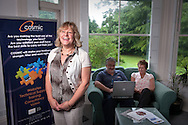 UK. Devon. Ottery St Mary. Julie Harris, Chief Executive of COSMIC, a Devon based technology business which offers ICT services to organisations with the aim of improving the way ICT is used to improve social, environmental and financial performance..Photo show Julie in their training centre with IT trainer (blue shirt and beard).