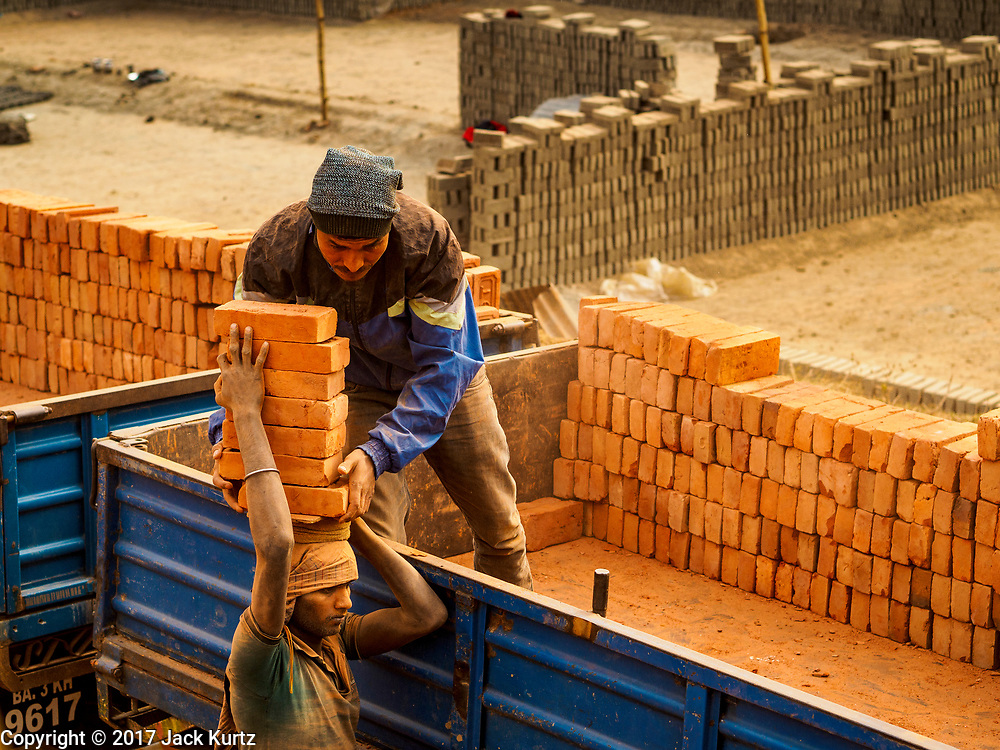 09 MARCH 2017 - BAGMATI, NEPAL:  A worker takes finished bricks to a waiting truck at a brick factory in Bagmati, near Bhaktapur. There are almost 50 brick factories in the valley near Bagmati. The brick makers are very busy making bricks for the reconstruction of Kathmandu, Bhaktapur and other cities in the Kathmandu valley that were badly damaged by the 2015 Nepal Earthquake. The brick factories have been in the Bagmati area for centuries because the local clay is a popular raw material for the bricks. Most of the workers in the brick factories are migrant workers from southern Nepal.           PHOTO BY JACK KURTZ