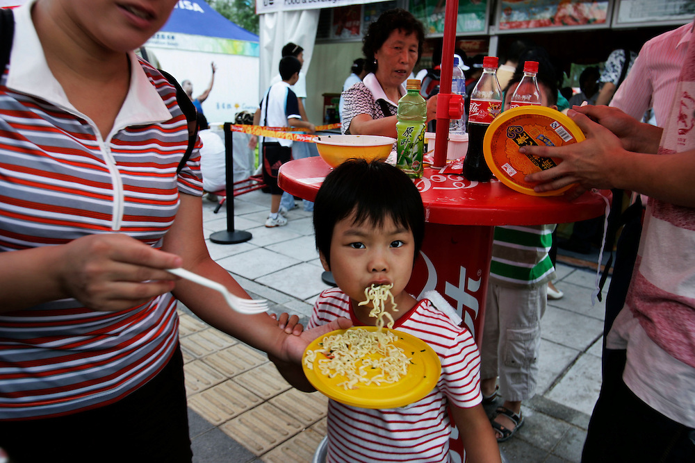 A Chinese child is fed instant noodles at a food stall at  the Olympic green in Beijing , China, Wednesday, Aug.20, 2008. It is one of the strangest things about the Olympics: From far away, it looks very close.Watching the Olympics on television, the athletes are right in front of you.  Up close, though, it's normally a different story. From the spectators' stands, the athletes are often just distant specks amid the enormity of some of the largest sports stadiums in the world. And there's so much else to grab your attention. There are snack bars,Coke machines, and life-sized cutouts of Chinese athletes with which you can pose. There are parades of Fuwas, the Olympic mascots. There are dancing fountains in front of the Water Cube, and thousands of volunteers to help you out.