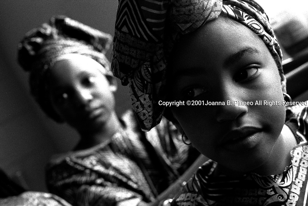 Girls in Richmond, Virginia in their African dress wait to begin the ceremony for their parents and friends.