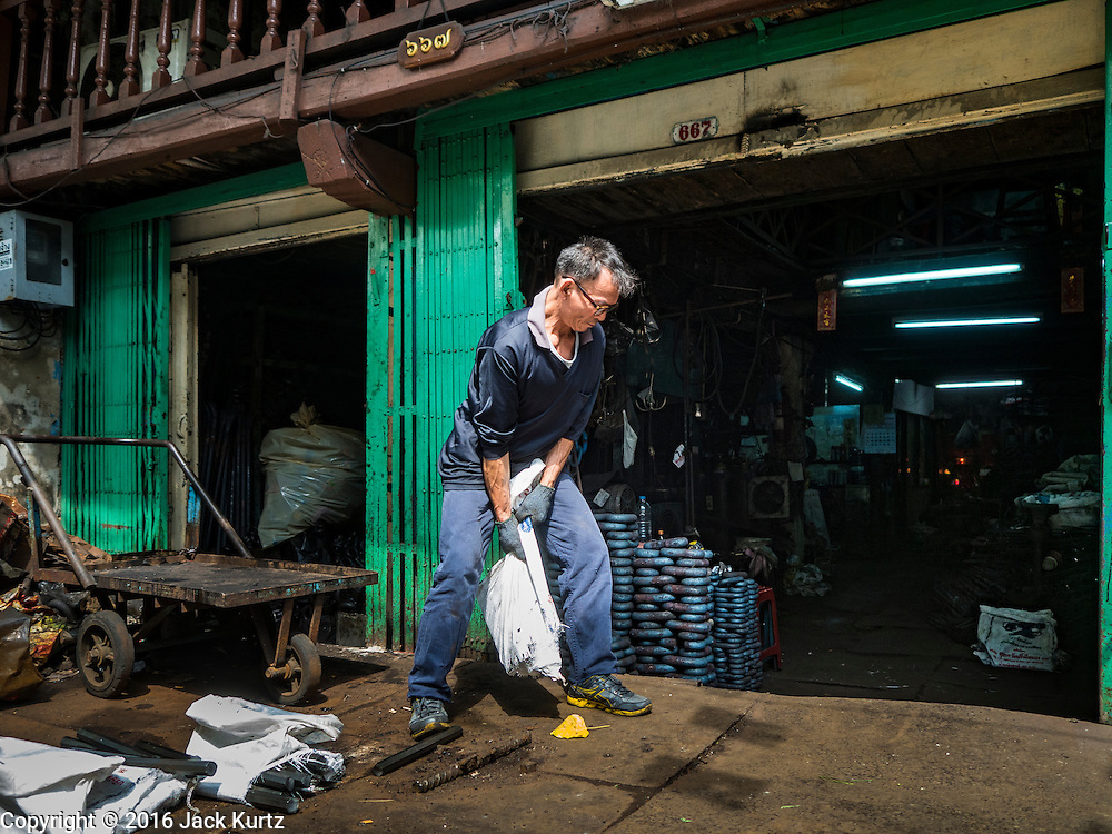 25 JANUARY 2016 - BANGKOK, THAILAND: The operator of a small one person workshop that makes heavy chains for boat anchors drags bags of metal into his shop to turn the metal into chain links. The metal for the chains is heated until it glows red and then it's pounded into shape. The Talat Noi neighborhood in Bangkok started as a blacksmith's quarter. As cars and buses replaced horse and buggy, the blacksmiths became mechanics and now the area is lined with car mechanics' and blacksmiths' shops.         PHOTO BY JACK KURTZ