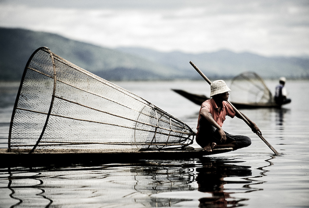 USE ARROWS &larr; &rarr; on your keyboard to navigate this slide-show<br /> <br /> Inle Lake, Myanmar - May 2006<br /> Burmese fishermen drive a boat in lake Inle. <br /> The fishermen are known for their technique of rowing wrapping one of the legs around the oar to relieve and free arms for fishing. <br /> Photo: Ezequiel Scagnetti