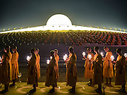 "11 FEBRUARY 2016 - KHLONG LUANG, PATHUM THANI, THAILAND: Buddhist monks participate in a candlelight procession around the pagoda during the Makha Bucha Day service at Wat Phra Dhammakaya.  Makha Bucha Day is a public holiday in Cambodia, Laos, Myanmar and Thailand. Many people go to the temple to perform merit-making activities on Makha Bucha Day, which marks four important events in Buddhism: 1,250 disciples came to see the Buddha without being summoned, all of them were Arhantas, or Enlightened Ones, and all were ordained by the Buddha himself. The Buddha gave those Arhantas the principles of Buddhism. In Thailand, this teaching has been dubbed the ""Heart of Buddhism."" Wat Phra Dhammakaya is the center of the Dhammakaya Movement, a Buddhist sect founded in the 1970s and led by Phra Dhammachayo. Makha Bucha Day is one of the most important holy days on the Thai Buddhist calender.      PHOTO BY JACK KURTZ"