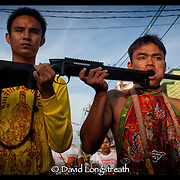 """In this """"Signature Series"""" image by David Longstreath, a devotee to the Phuket, Thailand Vegetarian Festival has his face pierced by a shotgun.  he annual festival in Phuket is held on a annual basis and begins usually in late September of early October depending on the lunar cycle."""