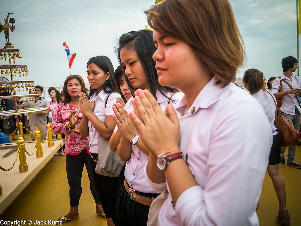 "27 NOVEMBER 2012 - BANGKOK, THAILAND:  School girls pray at Wat Saket during the temple's annual fair. Wat Saket, popularly known as the Golden Mount or ""Phu Khao Thong,"" is one of the most popular and oldest Buddhist temples in Bangkok. It dates to the Ayutthaya period (roughly 1350-1767 AD) and was renovated extensively when the Siamese fled Ayutthaya and established their new capitol in Bangkok. The temple holds an annual fair in November, the week of the full moon. It's one of the most popular temple fairs in Bangkok. The fair draws people from across Bangkok and spills out in the streets around the temple.   PHOTO BY JACK KURTZ"