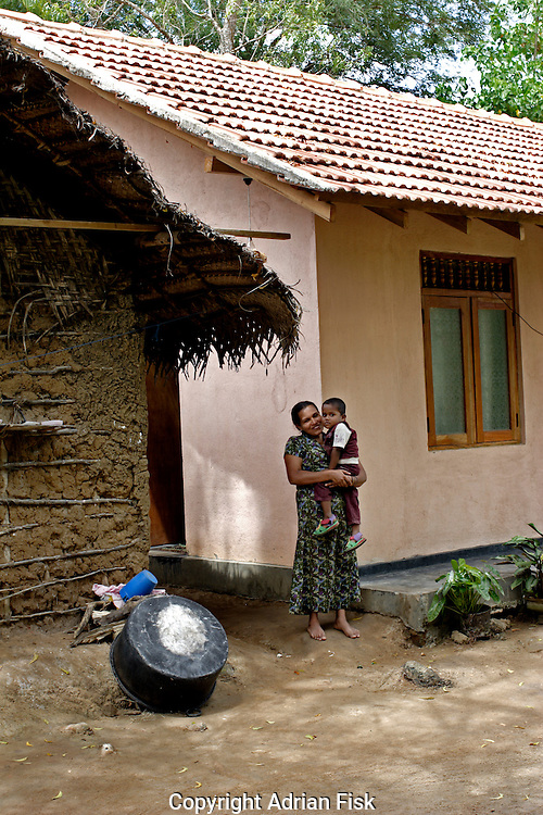 An Oxfam program of new housing shows the old beside the new. The house on the left comprising of two rooms housed a family of six. The new one on the right has four rooms and is protected from the harsh Sri lankan monsoon.
