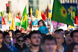 London, October 11th 2014. Thousands of protesters from the UK's Kurdish community demonstrate in London against the delay in assisting the people of the Syrian city of Kobane in their fight against ISIS. They also accuse Turkey, with whom the Kurds have had a long-running insurgency of siding with the Islamic State by doing nothing to help Kurds in Kobane. PICTURED: A little girl rides on an adult's shoulders as the march returns to Parliament Square.