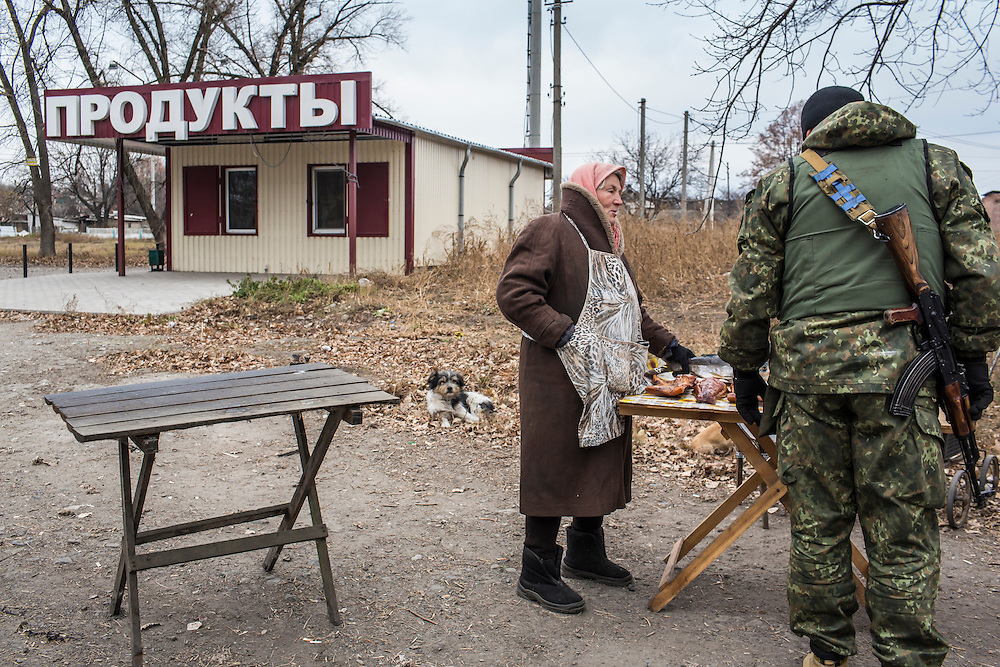 KARLIVKA, UKRAINE - NOVEMBER 17, 2014: A woman sells dried and smoked fish by the side of the road as a member of the Dnipro-1 brigade, a pro-Ukraine militia, peruses the goods in Karlivka, Ukraine. CREDIT: Brendan Hoffman for The New York Times