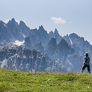 """A hiker admires sharp peaks of the Cadini Group in the Sesto Dolomites, Italy, Europe. In the Cadini di Misurina, Cima Grande rises to 2999 meters (9839 feet), between Cima Piccola and Cima Ovest. The Cadini Group is in the Sesto Dolomites (Dolomiti di Sesto, or Sexten/Sextner/Sextener Dolomiten) which lie north of the Fiume Ansiei valley, in the municipality of Auronzo. From the Rifugio Auronzo toll road, hike for spectacular views around Tre Cime di Lavaredo (Italian for """"Three Peaks of Lavaredo,"""" called Drei Zinnen or """"Three Merlons"""" in German). The Dolomites are part of the Southern Limestone Alps. UNESCO honored the Dolomites as a natural World Heritage Site in 2009."""