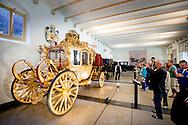 APELDOORN - APELDOORN - Details van de Gouden Koets in het museum bij Paleis Het Loo bij de tentoonstelling Paardenkracht en Autopracht. Na Prinsjesdag zal de koets drie tot vier jaar in onderhoud gaan. De Gouden Koets is na Prinsjesdag drie tot vier jaar uit de roulatie voor groot onderhoud. Volgens de Rijksvoorlichtingsdienst (RVD), is onder meer het houtsnijwerk toe aan een opknapbeurt. De voorziene kosten voor de restauratie vallen volgens de RVD binnen de reguliere begroting van de Dienst van het Koninklijk Huis. Volgens de RVD gaat het onder andere om &ldquo;intensieve restauratiewerkzaamheden&rdquo; aan het houtsnijwerk en de wielen. Ook worden de draagriemen aan de kast en de koorden en de kwasten op de bok vervangen en worden de textiele materialen onder handen genomen.<br /> Glazen koets<br /> <br /> Behalve komende Prinsjesdag is de Gouden Koets voor het publiek nog te zien tijdens het evenement Paardenkracht en Autopracht in Nationaal Museum Paleis Het Loo van 27 tot en met 30 augustus. Tijdens de restauratie zal de net opgeknapte Glazen Koets worden gebruikt voor ceremoni&euml;le taken, zoals Prinsjesdag.<br /> <br /> De Gouden Koets is een geschenk van de inwoners van Amsterdam aan koningin Wilhelmina ter ere van haar inhuldiging in 1898. Op 7 februari 1901 werd de Gouden Koets voor het eerst gebruikt bij het huwelijk van koningin Wilhelmina en prins Hendrik.<br /> <br /> De komende jaren richt het onderhoud van de koets zich op vier onderdelen: het onderstel, de kast, de stoffering en de bok.  <br /> The Golden Carriage of The Netherlands at Palace het Loo for the exhibition &lsquo;The Power of the horse, the beauty of the car in Apeldoorn, The Netherlands, 2 september 2015. The Golden Carriage will be used at Prinsjesdag 15 september for the last time by King Willem-Alexander, after that it will be restored for years. The Golden Carriage will bring the Dutch King and Queen to the 'Ridderzaal' (Hall of Knights) on 'Prinsjesdag' (Prince's Day) in The H