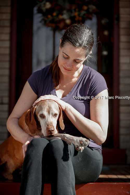 SHOT 2/21/17 2:21:01 PM - Tanner, a 12 year-old male Vizsla, with his mom Margaret Ebeling in Denver, Co. The Vizsla, is a dog breed originating in Hungary. The Hungarian or Magyar Vizsla represents one of the best in sporting dogs and loyal companions and has a strong claim to being one of the smallest of the all-round pointer-retriever breeds. The Vizsla's size is one of the breed's most attractive characteristics and through the centuries he has held a unique position for a sporting dog -- that of household companion and family dog. The Vizsla is a natural hunter endowed with a good nose and an above average trainability. Although they are lively, gentle mannered, demonstrably affectionate and sensitive, they are also fearless and possessed of a well-developed protective instinct.<br /> (Photo by Marc Piscotty / &copy; 2017)