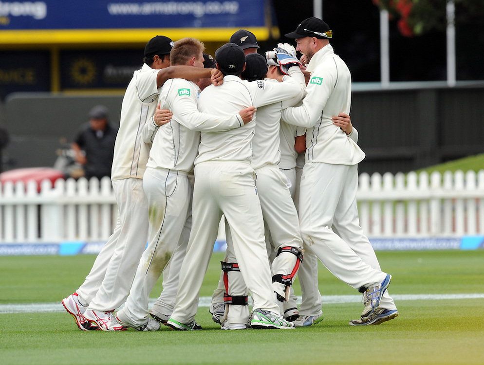 The New Zealand team gather around Trent Boult after he took the catch to dismiss West Indies Denesh Ramdin for 19 on the third day of the second International cricket match, Basin Reserve, Wellington, New Zealand, Friday, December 13, 2013. Credit:SNPA / Ross Setford