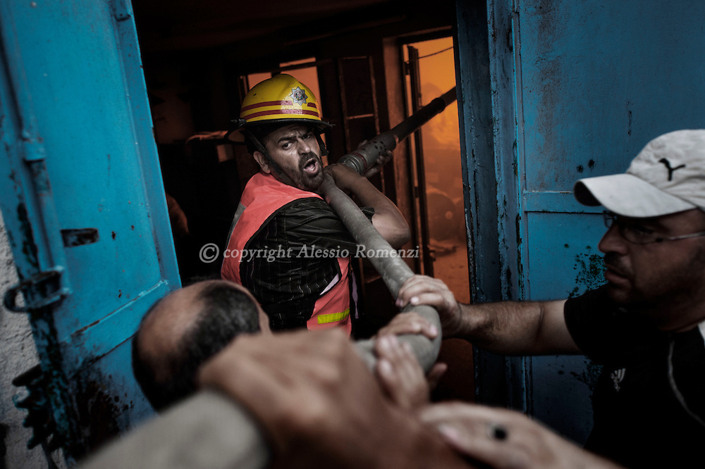 Gaza Strip, Gaza City: A firefighter try to shut off a fire inside a soap factory in Gaza City after was hit by an Israeli airstrike on August 10, 2012. ALESSIO ROMENZI