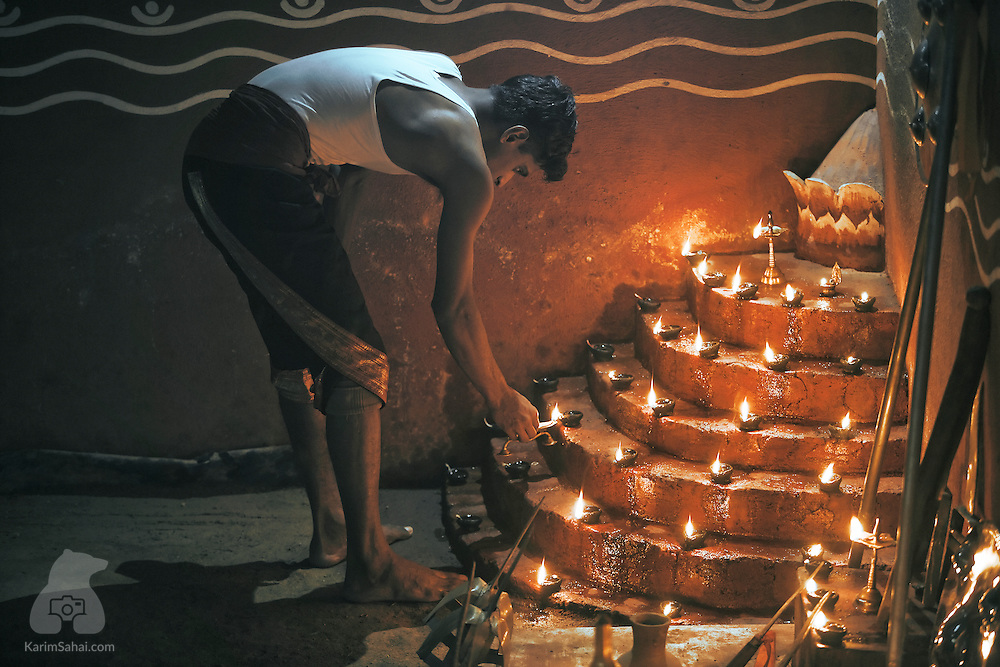 A Kalaripayat (martial arts) fighther lights rows of deepam (votive lights) before staring his training session in Kumily, Kerala, India.<br /> <br /> The kalari (traing ground) is considered a sacred place. Especially revered is the south-west corner called the poothara, which is reserved for the reigning deity and here the weapons are stored under his protection. Next to this is the guruthara, the place where lamps are kept burning in reverence to all the gurus of the kalari.