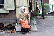"A ""Babushka"" (Russian old woman) keeps an eye on things from her property in Tomsk, Siberia. June 2001."