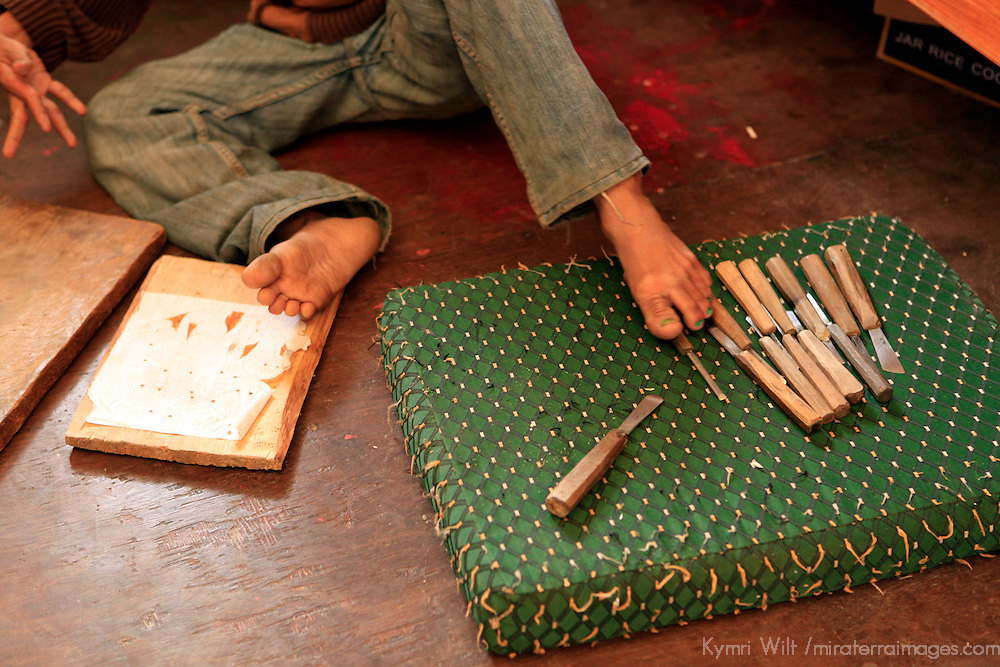 Asia, Bhutan, Thimpu. Disabled woodcarver uses his feet at the National Institute for Zorig Chusum, or traditional arts and crafts.