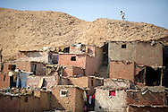 A boy runs along the Muqattam cliffs in the Manshiet Nasser slums on eastern outskirts of Cairo, Egypt, on October 5, 2011. Along with the threat of another rock slide, residents live without basic public services such as water supply and waste management. Ann Hermes/© The Christian Science Monitor 2011