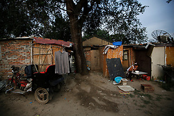 A picture made available on 30 July 2013 of a Chinese resident sitting outside her home in a slum or shanty town area by the second ring road of Beijing, metres away from the prosperous Central Business District (CBD), separated only by a busy highway in China, 29 July 2013. Beijing announced plans to spend 500 billion yuan (61.5 billion euros) to renovate shanty towns within the fourth ring road according to local media. The five-year plan is expected to affect more than 230,000 households. China's massive urbanization push has resulted in the creation of large pockets of shanty towns and slums in urban areas as millions of migrant workers shifting to the cities are often priced out of city-centre properties. Slum or shanty town dwellers often live in dirty and cramped conditions, where they have no running water in their homes and have to share toilet and shower facilities.