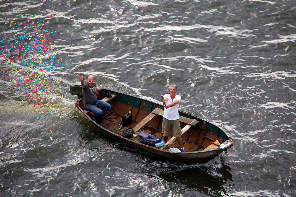 Europe, Netherlands, Amsterdam. Boaters celebrate a cruiseship sailaway from Amsterdam.