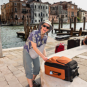 Woman with rolling luggage in Venice, Italy, Europe. Venice (Venezia), founded in the 400s AD, is capital of Italy's Veneto region, named for the ancient Veneti people from the 900s BC. The romantic City of Canals stretches across 100+ small islands in the marshy Venetian Lagoon along the Adriatic Sea, between the mouths of the Po and Piave Rivers. The Republic of Venice was a major maritime power during the Middle Ages and Renaissance, a staging area for the Crusades, and a major center of art and commerce (silk, grain and spice trade) from the 1200s to 1600s. The wealthy legacy of Venice stands today in a rich architecture combining Gothic, Byzantine, and Arab styles. Venice and the Venetian Lagoon are honored on UNESCO's World Heritage List. For licensing options, please inquire.