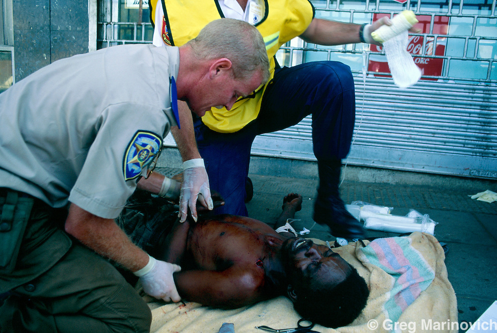 Johannesburg, South Africa, 1994. Medics treat the wounded  African National Congress guards opened fire on Inkatha Freedom Party marchers when they approached the ANC headquarters of Shellhouse, Johannesburg 1994. Many IFP supporters killed and wounded. Others were shot from the rooftops by persons unknown at the nearby Library Gardens. Johannesburg, South Africa