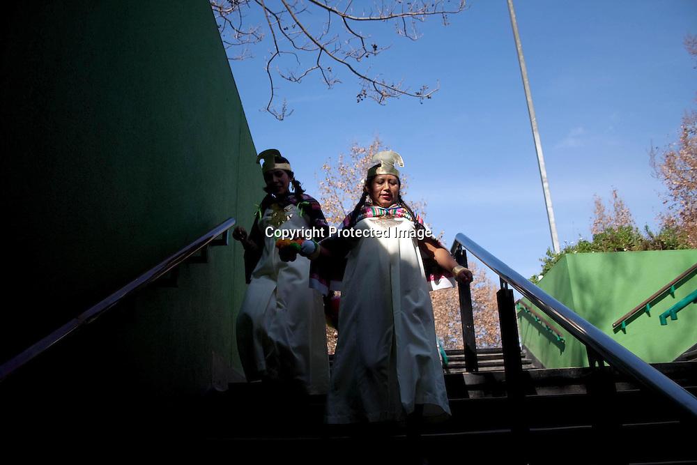 Algunos inmigrantes peruanas asesoras del hogar, con diferentes tipos de fechas de residencia y edades  participan de un baile religioso en Santiago de Chile, para darle honores  a la virgen del Carmen, viajando en el metro (medio de transporte) con sus vestimentas festivas, dándole color y más vida a la cotidianidad.