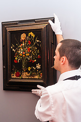 """Sotheby's London, November 28th 2014.Sotheby's hold a preview for their December 3rd sale of Old Master and British Paintings at their Bond Street gallery. The exhibition runs from November 29th to December 3rd. PICTURED: A Sotheby's gallery tedchnician hangs Ambrosius Bosschaert the Elder's """"Still life of flowers including irises, lillies, narcissi, lilly-of-the-valley and carnations in a tall glass vase, set on a stone ledge"""", which was painted in 1606. It has an estimated value of up to £900,000 at auction."""