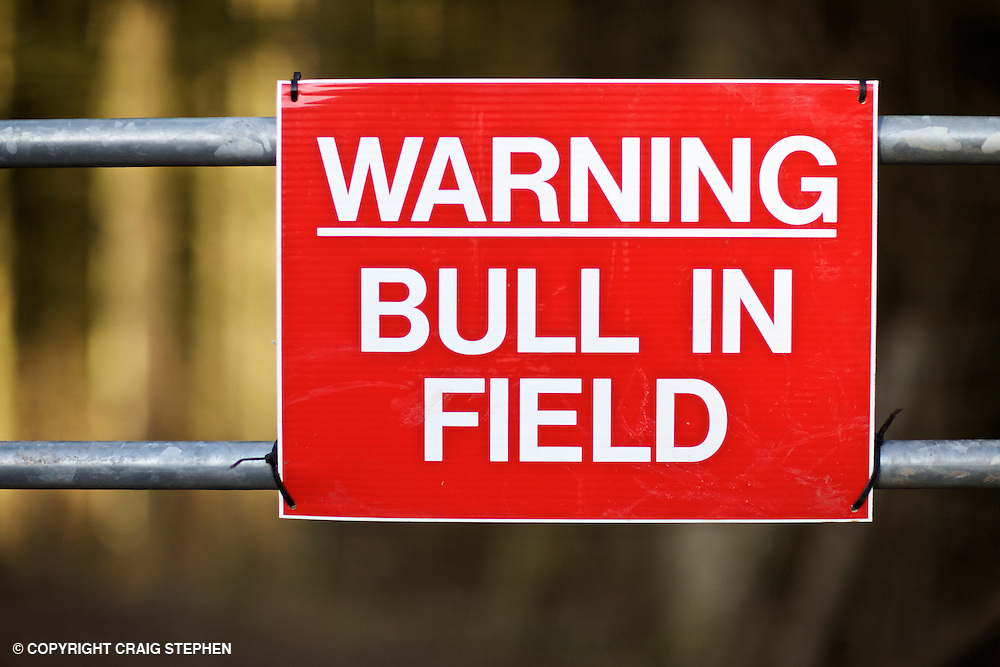 """red """"warning bull in field"""" sign on farm gate"""