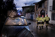 Volunteers of the civil protection walk into the small town called Onna damaged during a eartquake earlier in the day on April 6, 2009. A violent earthquake jolted central Italy killing at least 100 people and injuring 1,500 as buildings and homes in the walled medieval town of L'Aquila were reduced to rubble..© ALESSIO ROMENZI
