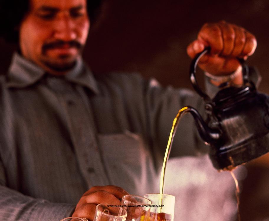 Tea is omnipresent in Saudi Arabia.  A family member of the Shammar serves black tea sweetened with sugar. Nafud, Saudi Arabia