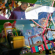 """Fairgoers at the midway are reflected in the glass case of the """"Mighty Payloader"""" as Shawn, who didn't want to give his last name, tends the booth."""