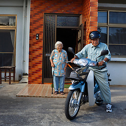 Fumi Tamaki escorts her husband, farmer Shimpuku Tamaki, 98, as he leaves home on his motorbike to check on his crops.