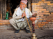 12 MARCH 2017 - BHAKTAPUR, NEPAL:  A Nepali man smoke a water pipe and watches the Holi celebration in Bhaktapur. Holi, a Hindu religious festival, has become popular with non-Hindus in many parts of South Asia, as well as people of other communities outside Asia. The festival signifies the victory of good over evil, the arrival of spring, end of winter, and for many a festive day to meet others. Holi celebrations in Nepal are not as wild as they are in India.    PHOTO BY JACK KURTZ